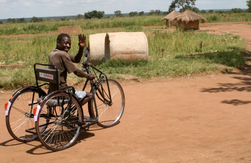 African man in a wheelchair waving to the camera.