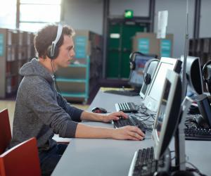 Man wearing a headset and focusing on a computer-based training.