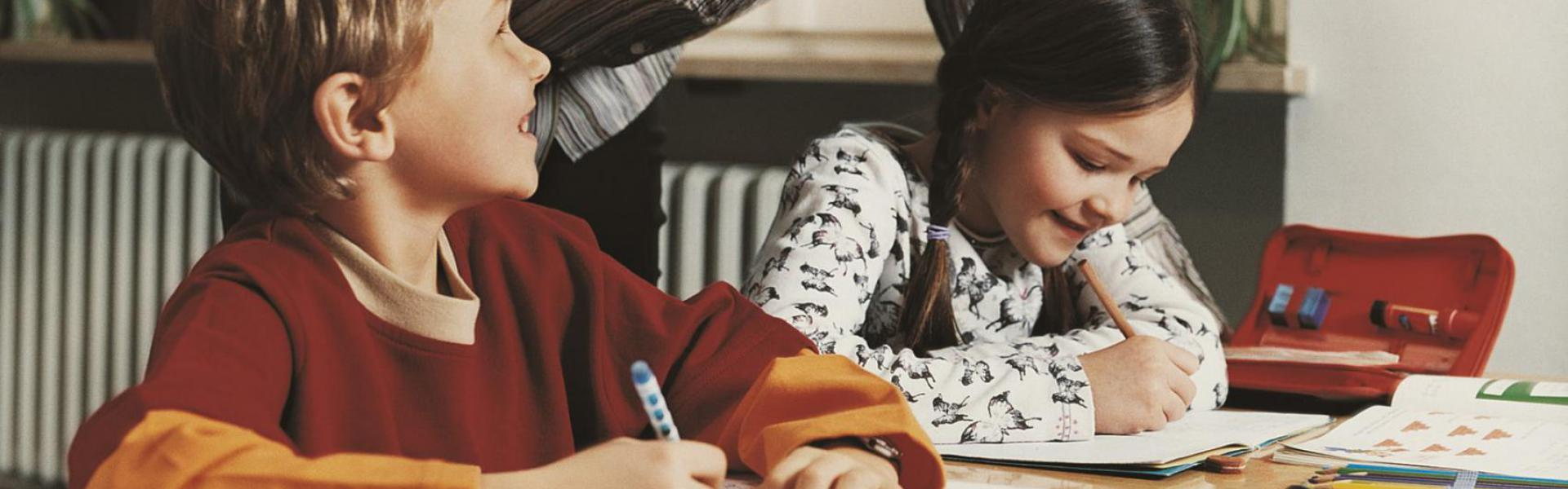 A girl and a boy studying with their teacher helping.